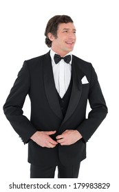 Happy groom in tuxedo getting ready over white background