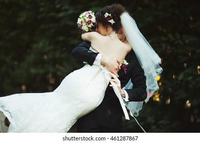 Happy groom whirls an elegant bride