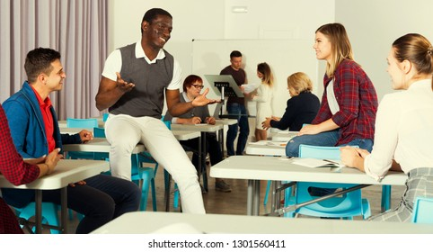 Happy group of adult students lively chatting while enjoying free time in class