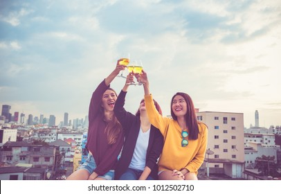 Happy group of asia girl friends enjoy laughing and cheerful toast sparkling wine glass at rooftop party,Holiday celebration festive,teeage lifestyle,freedom and fun