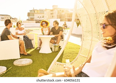 Happy group of attractive friends drinking and socialising outdoors on a green lawn during a warm summer evening during sunset.