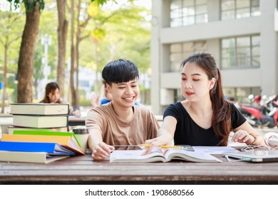 A happy group of attractive young people is tutoring exams with study books, sitting on the study table. Student group and tutoring education concept.