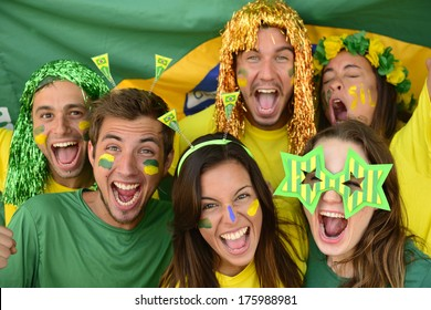 Happy group of Brazilian sport soccer fans amazed celebrating victory together.