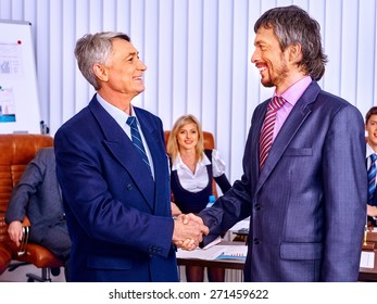 Happy group business people in office.Handshake of two people.