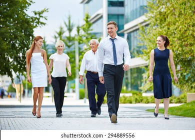 Happy group of business people walking in front of the office