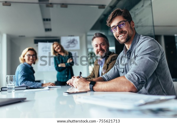 Happy group of businesspeople during presentation. Colleagues looking at camera and smiling.