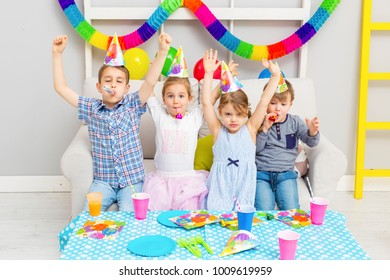 Happy group of children celebrating friends birthday. Kids party
