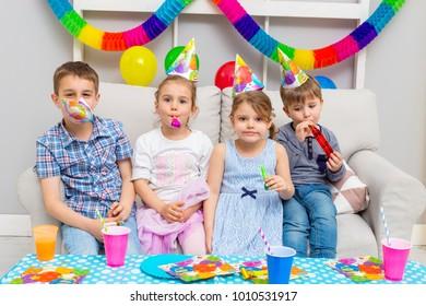 Happy group of children celebrating friends birthday. Kids party