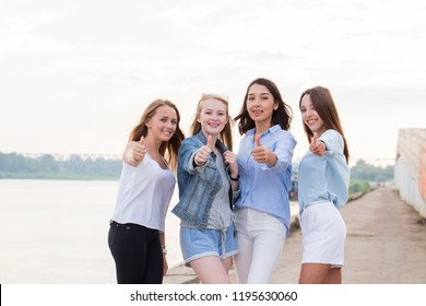 Happy group of female friends with thumbs up outdoor looking at camera and smile. Young girl student after College