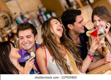 Happy group of friends at the bar having drinks