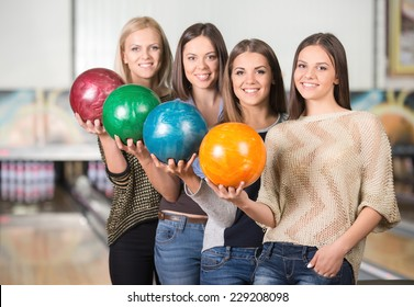 Happy group of friends bowling and are holding balls.