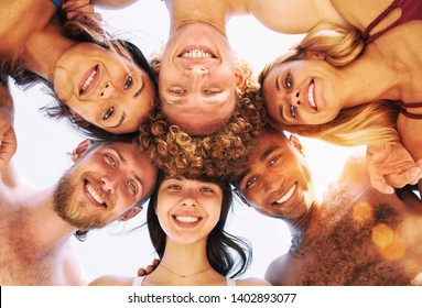 Happy group of friends in circle under the sun in the summertime