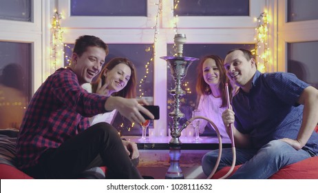 Happy group of friends doing selfie with mobile phone and smoking hookah in a night bar with beautiful bokeh lights