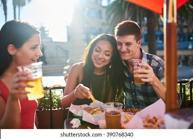 happy group of friends eating food and drinking beer at bar or pub