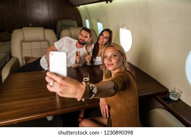Happy group of friends having party on a luxury private jet