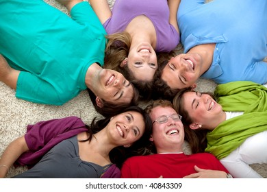 happy group of friends with heads together on the floor