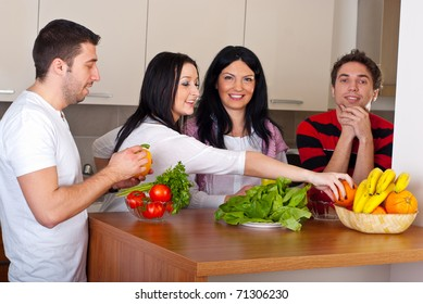 Happy group of friends  preparing food with fresh vegetables and having conversation in kitchen
