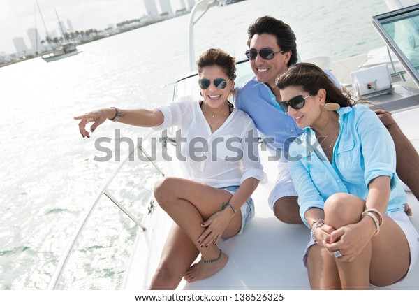 Happy group of friends sailing on a boat and pointing away