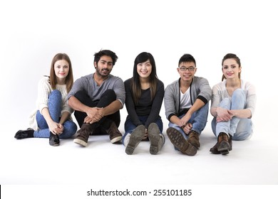 Happy group of friends sitting on floor. Mixed race group. Isolated on a white background.