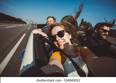 Happy group of friends taking selfie when road trip in convertible car. Cheerful students having fun when travel in Europe.