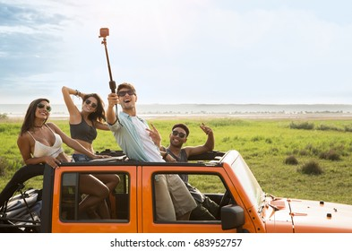 Happy group of friends taking selfie during road trip in convertible car
