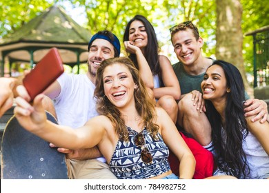 Happy group of friends taking a selfie. Multi ethnic people enjoying time together and laughing in London. Carefree and lifestyle concepts with real people