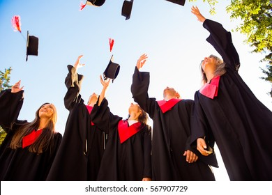 Happy group of graduated young students throwing hats in the air.