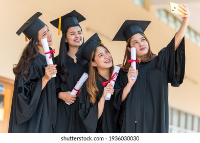 Happy group of graduates Asian student in academic gown and graduation cap holding diploma and Take a selfie