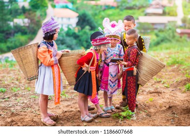Happy group of hill tribe kid wearing a Hmong dress carry bamboo basket Everyone watching smartphone on hill with their village at Phuhinrongkla National Park in Phitsanulok,Thailand. August 12, 2018