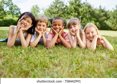 Happy group of interracial children happily lie at meadow
