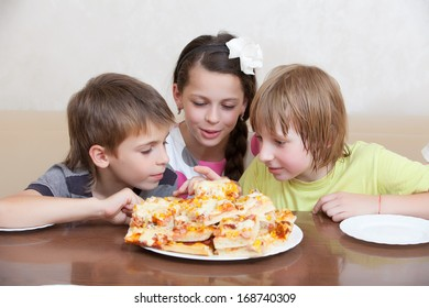 Happy group of kids eating pizza and smiling