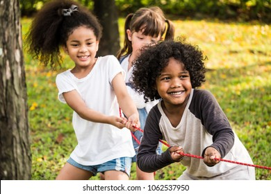 Happy group of kids playing tug of war in a park