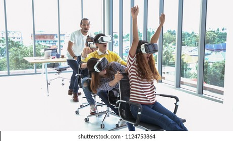 happy group of Multi Ethnic people have fun and ride on office chair while wear vr glasses