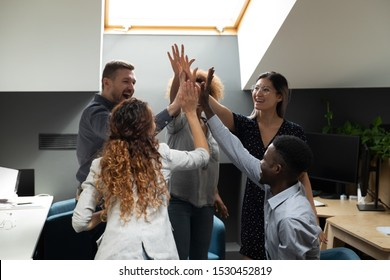 Happy group of multi-ethnic office workers standing in co-working open space stack palms together express unity, giving high five gesture of sharing common success and team spirit concept