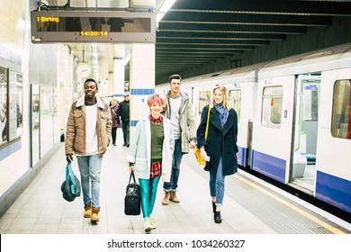 Happy Group of Multiracial Hipster Student Friends Walking at Tube Subway Station in London UK. Urban Best Friendship Concept with Young People Enjoying, Having Fun Together in City Underground Area.