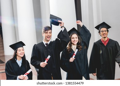 happy group on students gesturing and celebrating graduation while holding diplomas