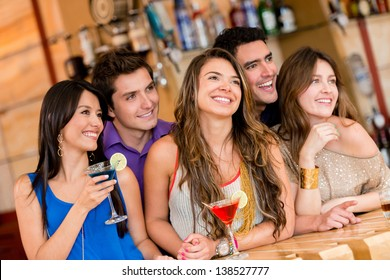 Happy group of people at the bar having a drink