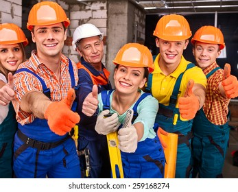 Happy group people in builder uniform thumb up.