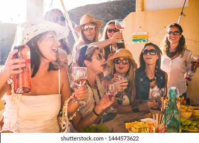 Happy group of people celebrate a birthday. Smiling women with red wineglass. wooden table, food and drink. Friendship concept