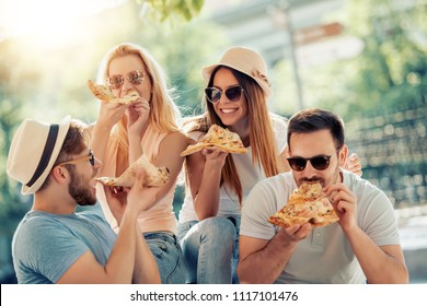 Happy group of people eating pizza outdoors,they are enjoying together.