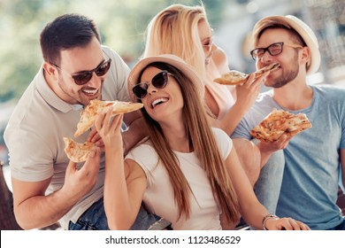 Happy group of people eating pizza outdoors,having great time together.