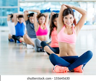 Happy group of people exercising at the gym