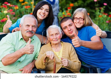 Happy group of people - family and doctor - showing thumbsup for the high quality services in the residential home.