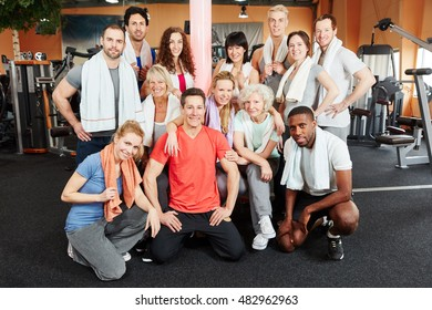 Happy group of people at the gym with trainer and senior women