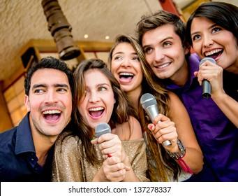 Happy group of people karaoke singing at the bar