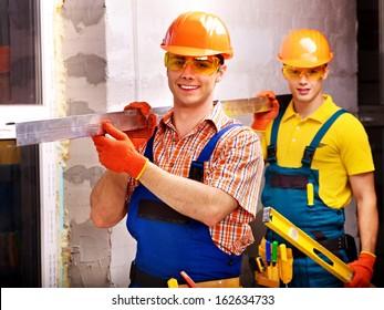 Happy group people men in builder uniform indoor.