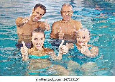 Happy group with senior couple in water holding their thumbs up