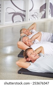Happy group of senior people doing crunches in a gym