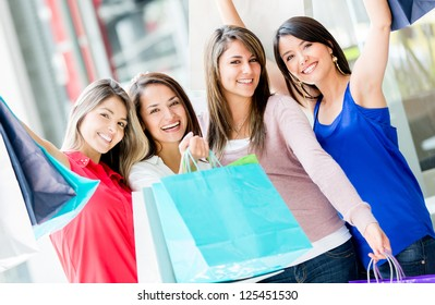 Happy group of shopping women with arms up