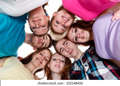 happy group of smiling friends holding heads together in circle